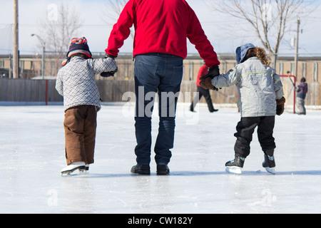 Avoir du plaisir en famille à la patinoire en plein air en hiver. Banque D'Images
