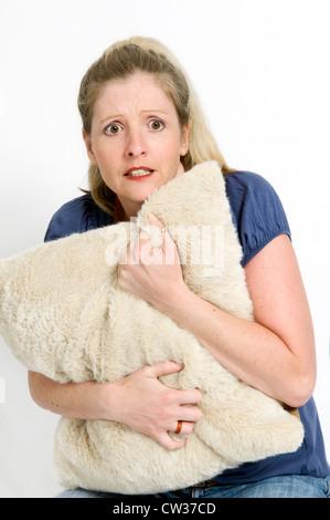 Close up of young woman Hiding behind coussin, concept d'être effrayé ou peur Banque D'Images