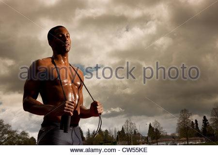 L'homme se reposant après le saut à la corde sur la voie Banque D'Images