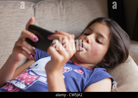 Jeune fille joue on mobile phone at home Banque D'Images
