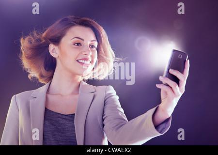 Young woman looking at cellphone avec lumières Banque D'Images