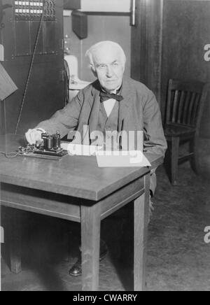 Thomas Edison, assis au bureau, démontrant un vieux télégraphe émetteur à son West Orange, New Jersey, de laboratoire, 1930.