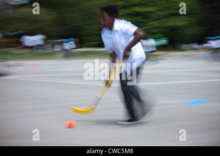 Un jeune garçon asiatique joue au hockey jeux pour enfants de son école, UK Banque D'Images