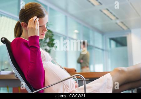 Femme enceinte assis au bureau Banque D'Images