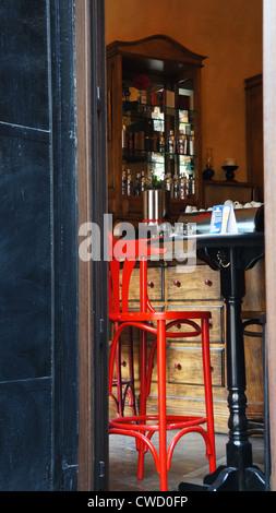 Un tabouret rouge dans un café-bar considéré de l'extérieur Banque D'Images