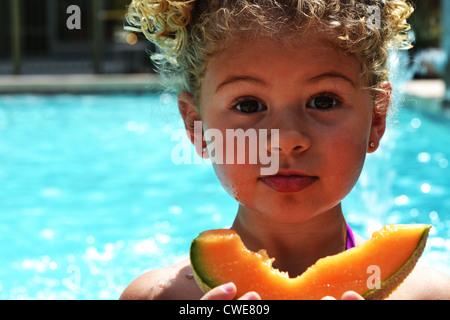 Cute Girl Eating Cantaloupe par un pool Banque D'Images