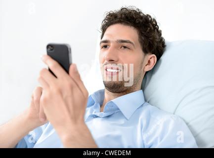 Jeune homme séduisant à l'aide de smart phone mobile moderne. Studio shot. Banque D'Images
