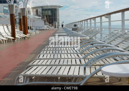 Bateau de croisière vide transats avec nettoyage de matelot, tôt le matin en mer Banque D'Images