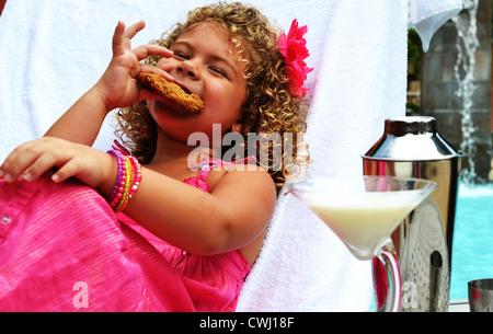 Une mignonne petite fille bénéficiant d'un cookie de la piscine avec un martini lait Banque D'Images