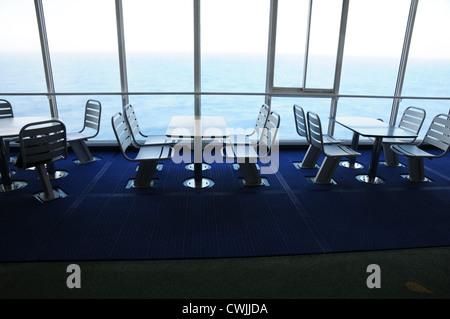 Tables et chaises en acier vide, fixé sur le pont, la fenêtre du sol au plafond, vue sur la mer, sol bleu foncé, Banque D'Images