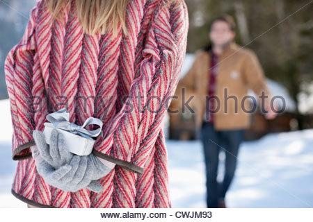 Approche de l'homme cadeau de Noël femme avec behind back Banque D'Images