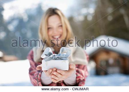 Portrait of smiling woman holding Christmas Gift en face de cabin Banque D'Images