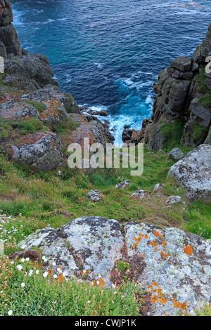 Vue depuis la falaise à Pordenack Point près de Lands End en Cornouailles avec des roches couvertes de lichen à Banque D'Images
