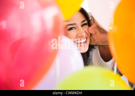USA, New Jersey, Jersey City, Man kissing woman colorful balloons Banque D'Images