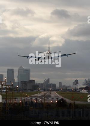 Avion à réaction à l'atterrissage à l'aéroport de London City, avec la piste en vue, et le quartier financier visible Banque D'Images