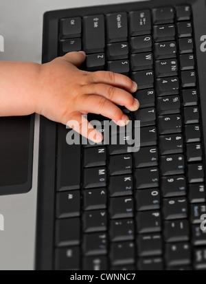 La main de l'enfant sur un clavier d'ordinateur portable Banque D'Images