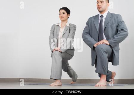 Young businesswoman and businessman doing yoga lunge côte à côte dans office Banque D'Images