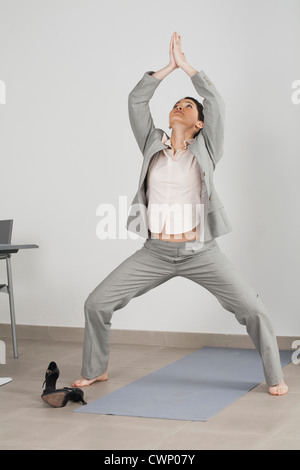 Businesswoman meditating in office Banque D'Images
