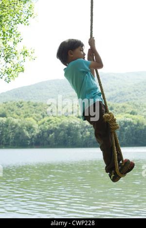 Garçon suspendu à corde sur river Banque D'Images