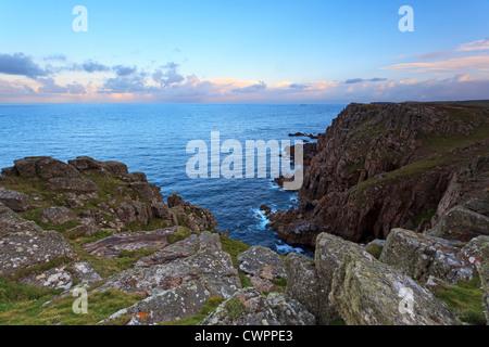 Pordenack Point près de Lands End en Cornouailles à la recherche vers les roches et les drakkars phare au lever Banque D'Images