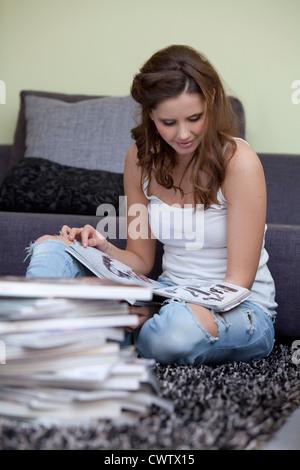 Young woman reading magazine dans la salle de séjour