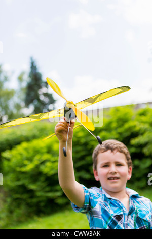 Boy Playing with toy airplane outdoors Banque D'Images