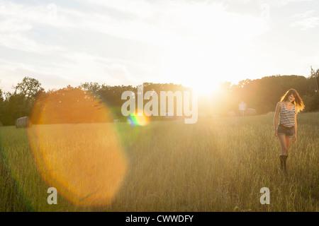 Smiling woman walking in grassy field
