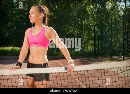 Femme au casque sur un court de tennis Banque D'Images