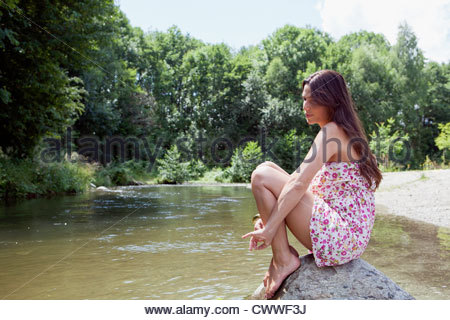 Teenage girl sitting on rock in stream Banque D'Images