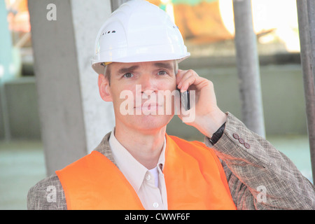 Businessman in hard hat on cell phone Banque D'Images