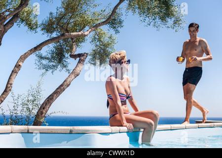 Couple par piscine extérieure Banque D'Images