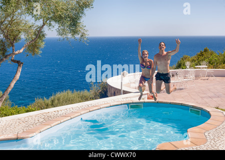 Couple jumping into swimming pool Banque D'Images