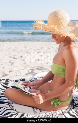 Woman using tablet computer on beach Banque D'Images