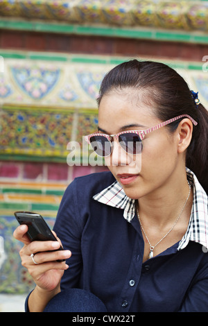Woman using cell phone at ornate temple Banque D'Images