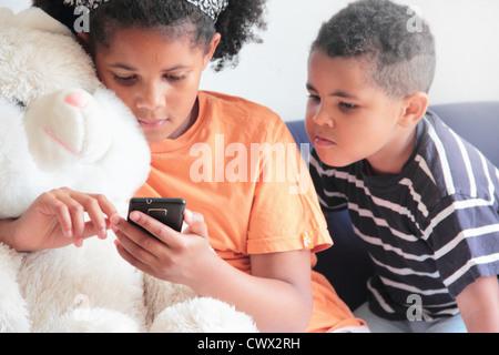 Garçon regardant sœur utiliser cell phone Banque D'Images