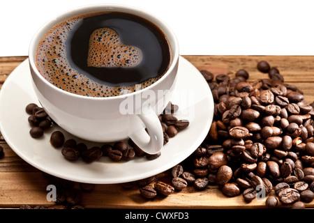 Tasse à café et soucoupe sur une table en bois. La mousse dans la forme du cœur.