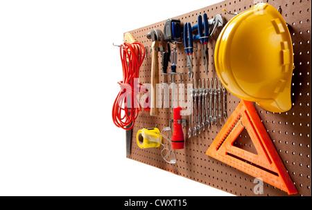 Peg board avec casque, rallonge, une lampe de poche, marteau, tournevis, bande, carpenter's square et pinces Banque D'Images
