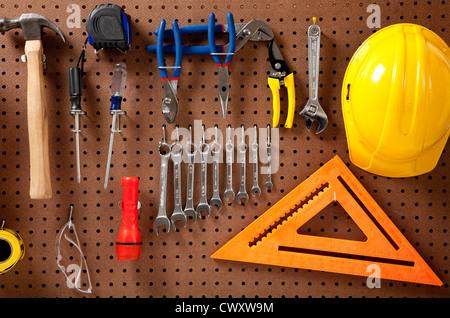 Une plaque avec divers outils tels que: marteau, clés, lampe, tournevis Banque D'Images