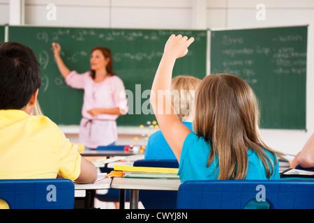 Fille de mettre sa main dans la classe Banque D'Images
