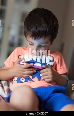 Jeune garçon joue à des jeux sur téléphone mobile