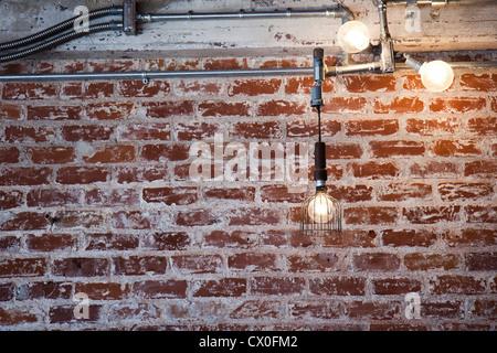 Ampoules lumineux suspendus dans l'avant du mur de brique Banque D'Images