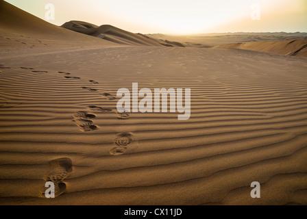 Des traces de pas dans le sable au lever du soleil dans le désert de Ramlat al-Sab'atayn, Yémen Banque D'Images