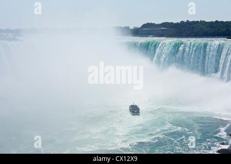 Maid of the Mist battant pavillon canadien à la fin de Horseshoe Falls Niagara chargés de touristes vêtus de ponchos Banque D'Images