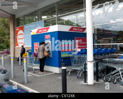 Jeune femme un retrait d'argent d'ATM, Greenfield, Greater Manchester, UK.