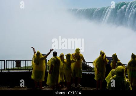 Les touristes vêtus de ponchos imperméables jaunes sur la plate-forme d'observation à la base de Niagara Falls, Banque D'Images