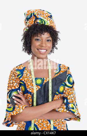 Portrait of young female fashion designer de vêtements imprimés africains debout les mains croisées sur fond gris Banque D'Images