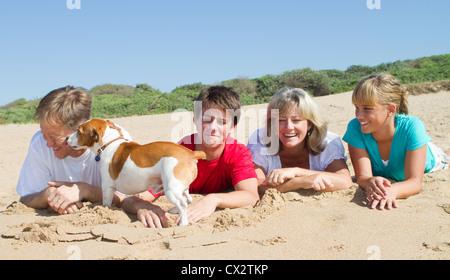 Famille de quatre personnes avec pet dog lying on beach Banque D'Images