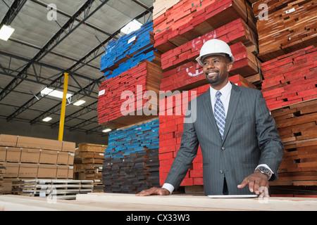 Un entrepreneur masculin debout devant des planches en bois empilées Banque D'Images
