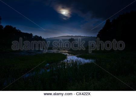 Lune avec nuages sur un marais dans le nord de l'Ontario Banque D'Images