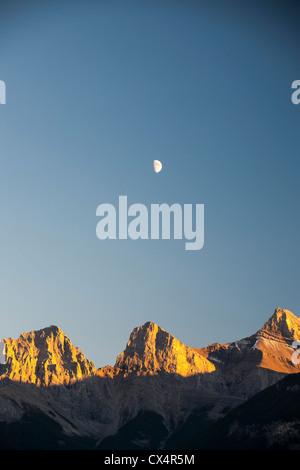La lune sur les trois Sœurs au-dessus de Canmore dans les Rocheuses canadiennes. Banque D'Images